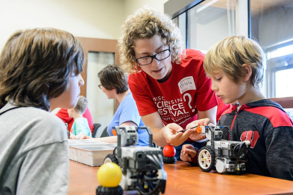 Photo of woman interacting with children at science festival by Bryce Richter from University Communications