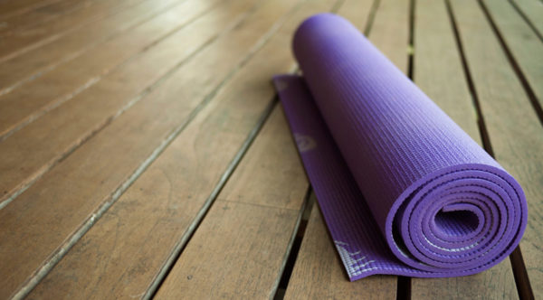 Photo of yoga mat on wooden floor by Cindybug via iStock