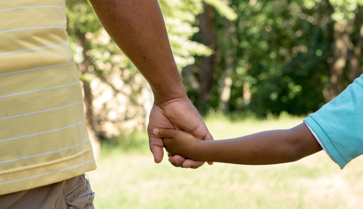 Photo of adult and child holding hands by pixelheadphoto via iStock