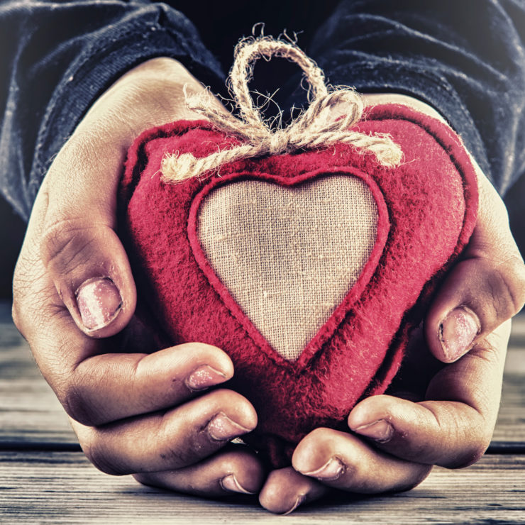 Photo of hands holding a red knitted heart to show that virtues are a necessary step for cultivating well-being