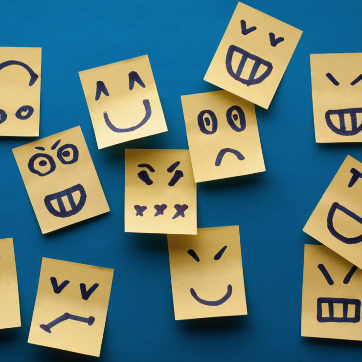Yellow sticky notes on a blue wall with different emotion expressions demonstrating that people experience may different emotions