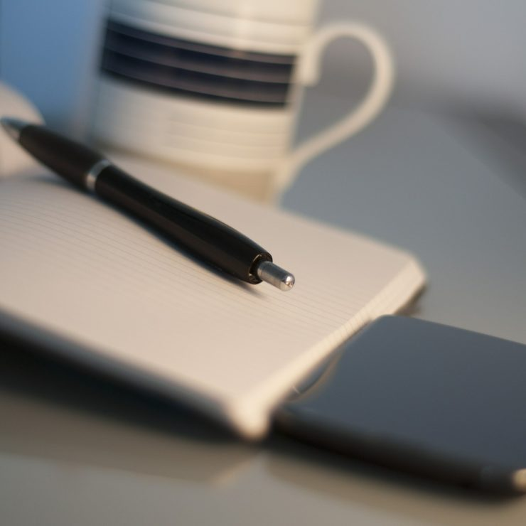A pen lying on top of a notebook to demonstrate good leadership