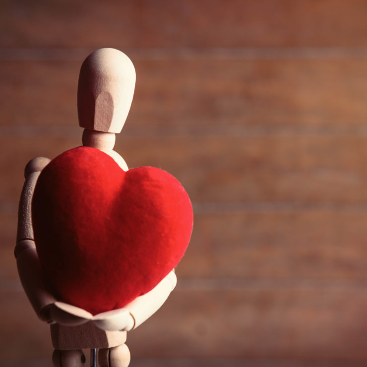 Wood stick figure holding a knitted red heart demonstrating the need for people to practice self-compassion.