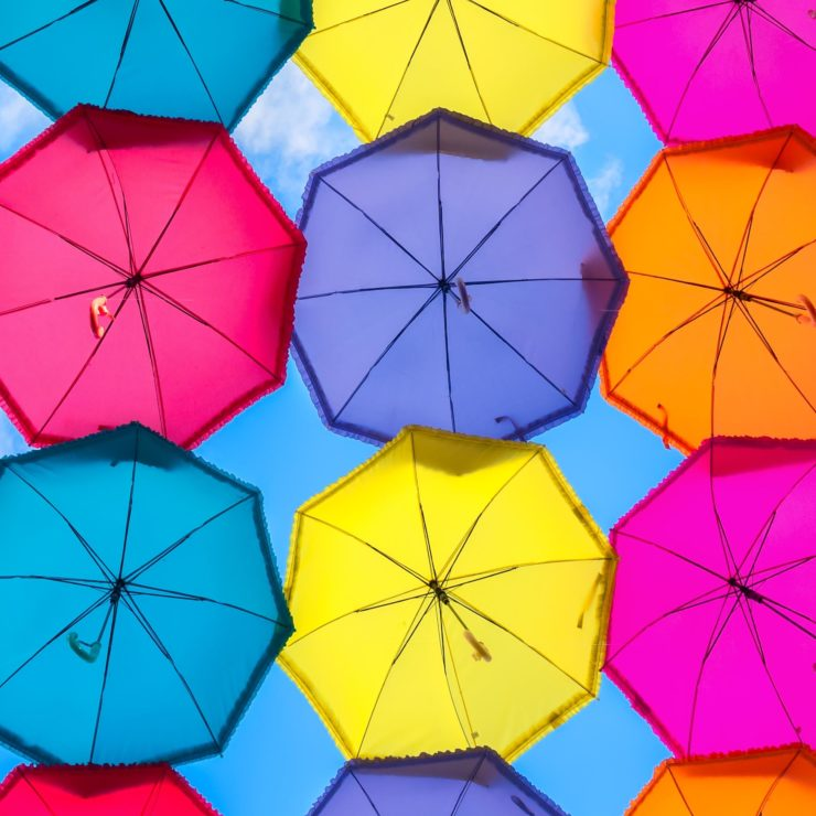 Underneath a canopy of multi-colored umbrella. This photo demonstrates how mindfulness can protect us from the negative impacts of a thought parade.