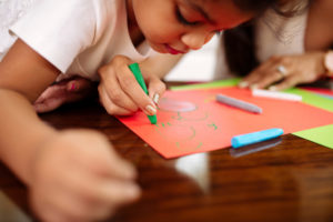 Child watching as an adult uses a green crayon to draw. This image demonstrates how adults can teach children well-being.