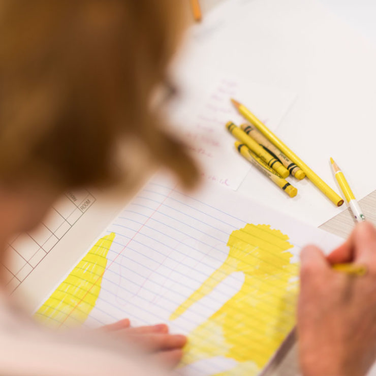 A Drawing Gym Participants Leans Over Her Notebook And Uses Yellow Crayons Markers And Colored Pencils