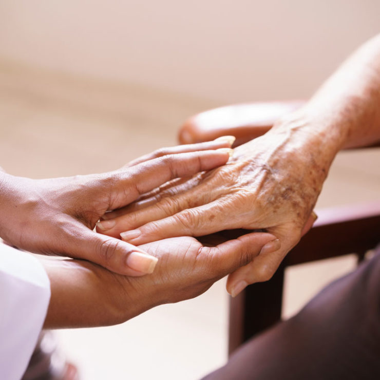 African American Doctor Holding The Hands Of An Elderly Person To Demonstrate End Of Life Care