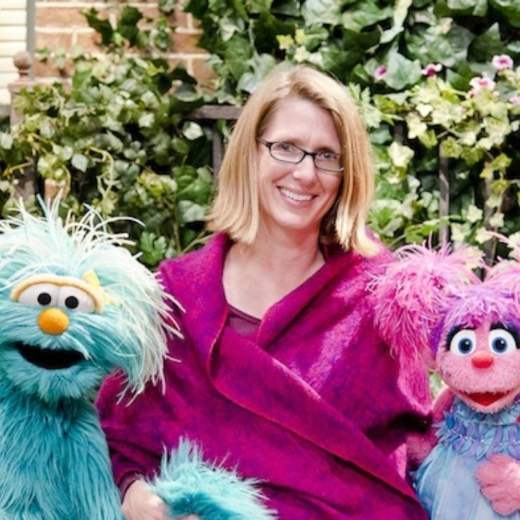 Center faculty member Julie Poehlmann-Tynan sits between two Muppets.