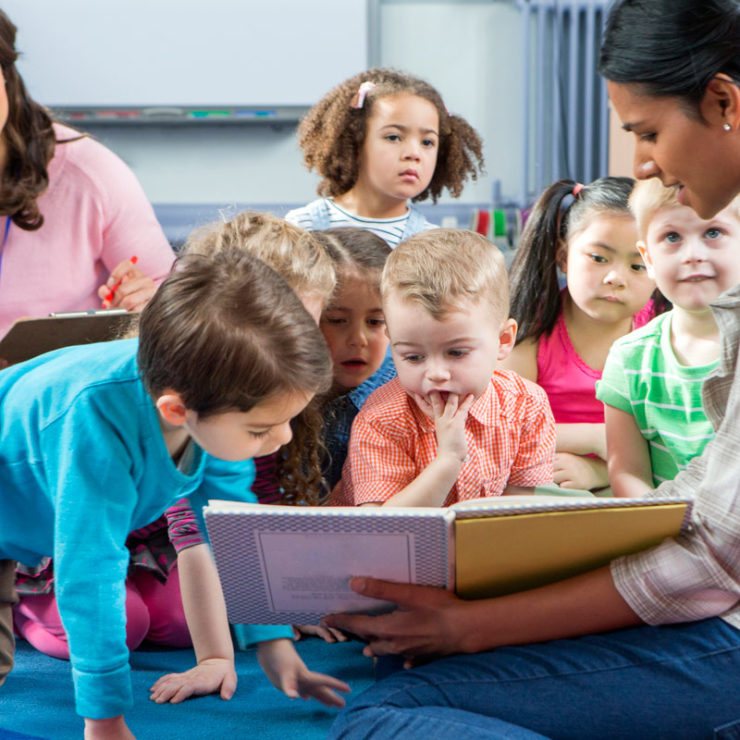 Children gathered around a teacher reading a book. This image demonstrates how teachers can incorporate the Center's Kindness Curriculum into their classrooms.
