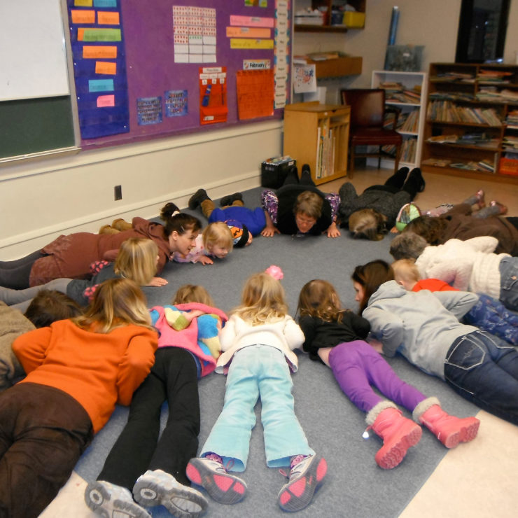 Children lying on their stomachs in a circle to depict a Kindness Curriculum practice.