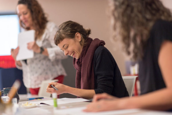 A Drawing Gym Participant Laughs As She Draws In Her Composition Notebook