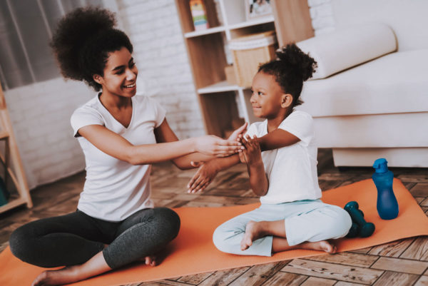 Mother Helping Her Daughter Do Yoga