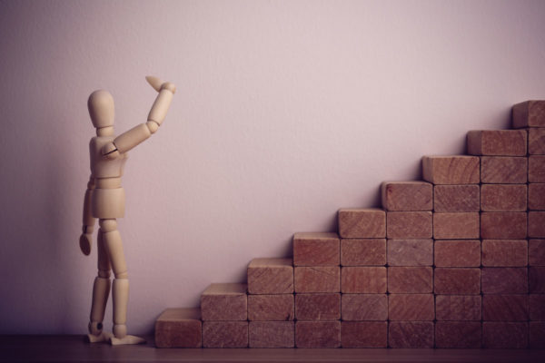 Wooden Figure Contemplating Climbing Stairs
