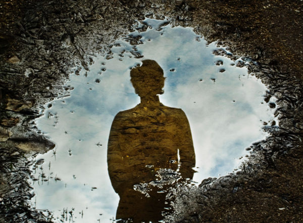 Photo of reflection of person in puddle by micaelnuss via iStock