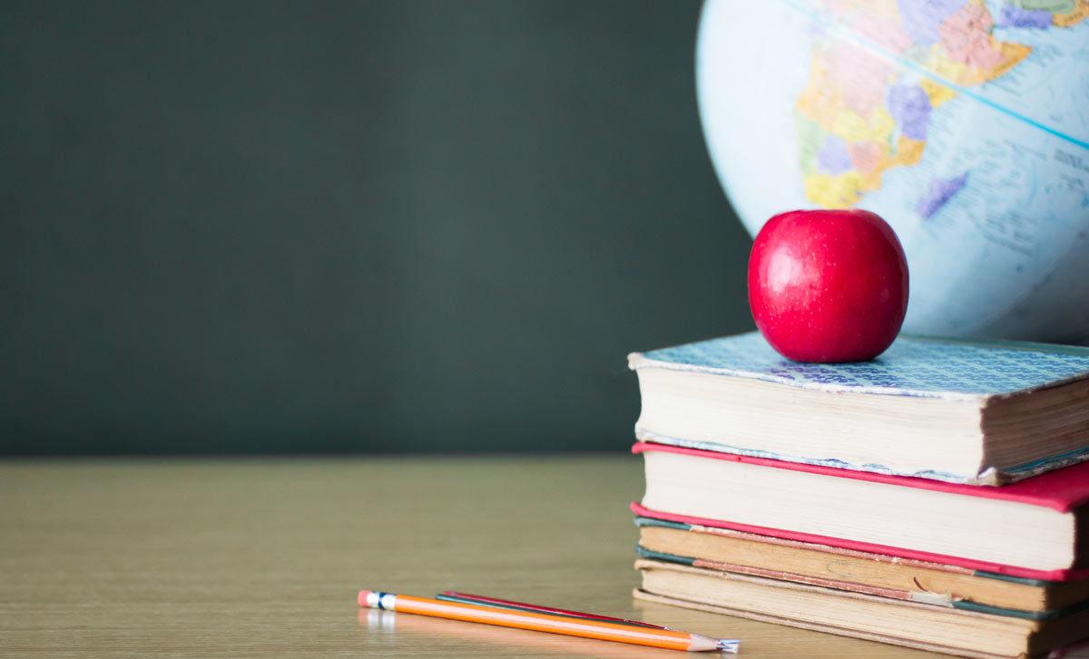 Classroom desk with apple by Andrea Carolina Sanchez Gonzalez via iStock