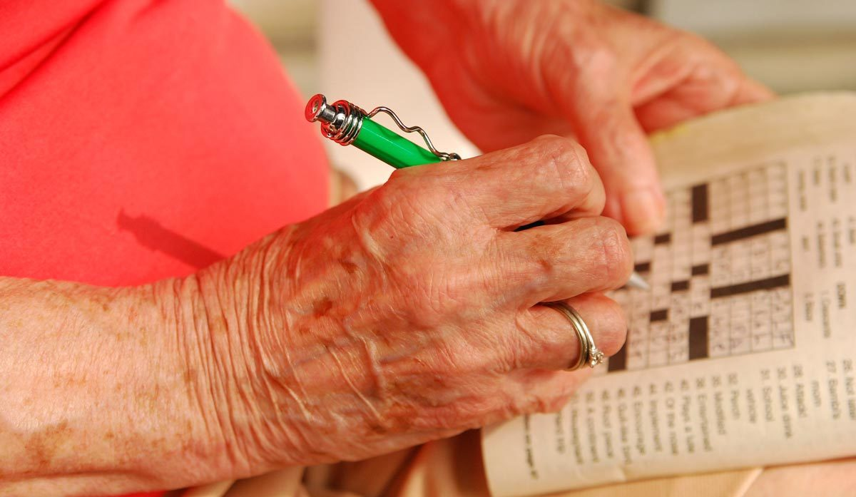 Woman doing crossword puzzle by plamensart via iStock