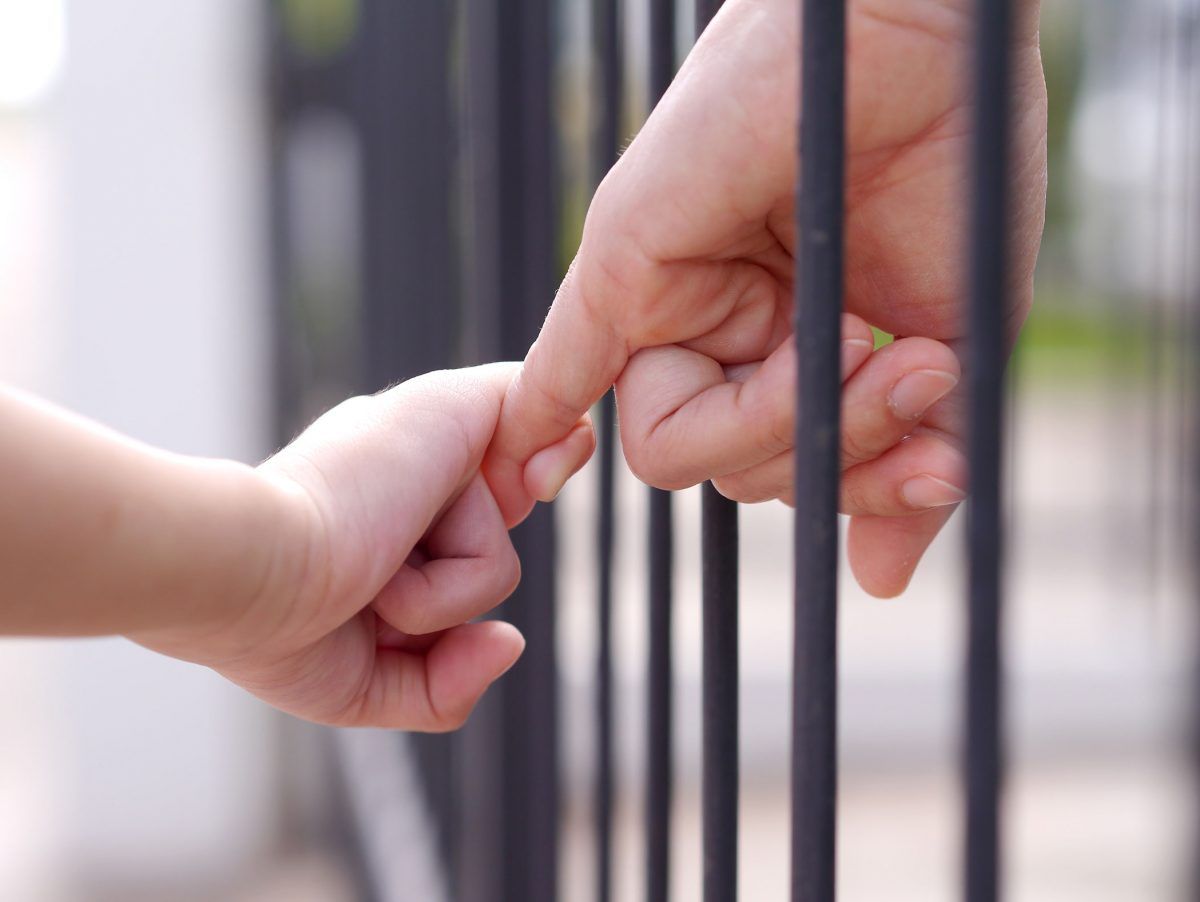 Parent And Child Linking Hands Through Bars