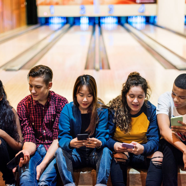 Teenagers Sitting In A Bowling Alley Depicting Well Being In Adolescents