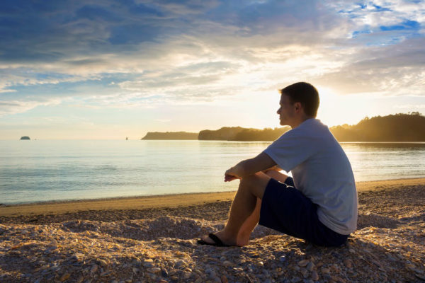Photo of a man looking out at water via  Istock